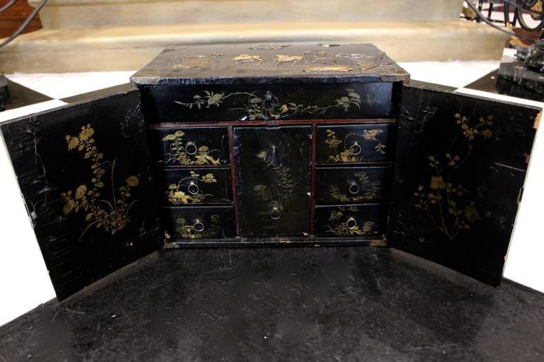 A late 18th century small Chinese black lacquered wood cabinet decorated with a raised animal scenery in a traditional landscape design. This cabinet of rectangular shape is elaborately inlaid with an array of colored stones in raised designs of