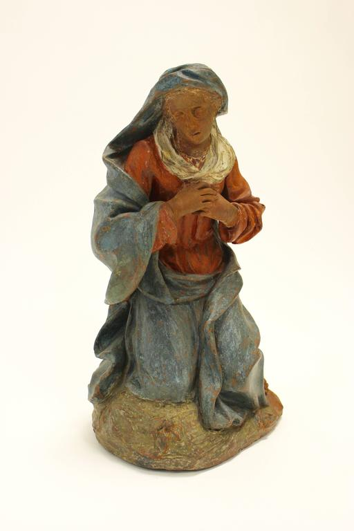 A 17th-18th century continental painted terracotta sculpture of a kneeling Virgin in the manner of Angolo di Poli. This exquisite terracotta sculpture features a poignant depiction of the Virgin Mary. The red and blue clothes that she is wearing