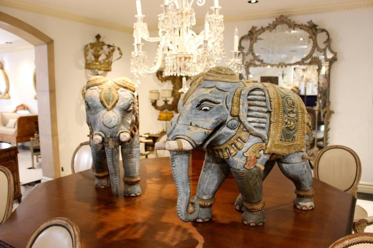 An exotic pair of striding wooden elephants sculptures carved and painted with exquisite detail. Wearing trinkets on the legs and tusks along with a large ceremonial necklace, each figure is caparisoned with an ornate yellow howdah blanket