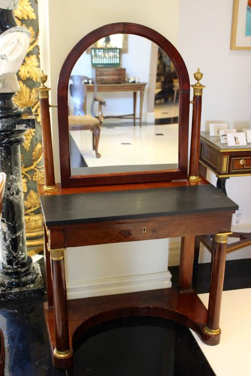 A French Empire period ormolu-mounted mahogany psyché dressing table from the early 19th century in neoclassical style. The rectangular black marble top is surmounted by an arched tilt mirror flanked by mahogany columns capped with urn finials above