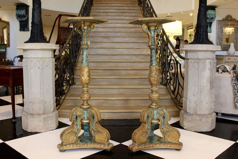 A pair of South European carved parcel-giltwood and faux-marble painted torchères from the late 18th or early 19th century. Carved all-over with gilt acanthus foliage, each piece features a hexagonal molded top shelf supported by three S-scroll