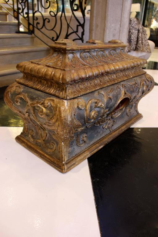 An Italian Rococo sarcophagus-shaped wooden chest of bombé rectangular form with richly carved gilt decoration on a distressed ebonized ground. The hinged pagoda top lid is skillfully carved with a frieze of urns in arches above a convex gadrooned
