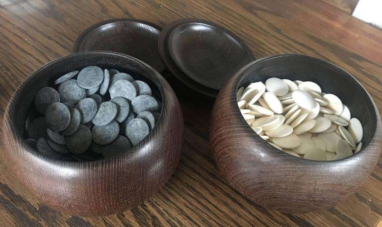 Beautiful set of Japanese go game playing chips made from shell and slate. Both chips are house in a simple wooden bowl with lid. Purchased at Takashimaya. 