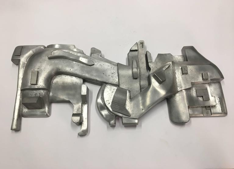 Beautiful wall sculpture made from cast aluminum by Michael Walsh.  Michael Walsh has been exhibiting extensively throughout North America and Europe since 1994. His work has been featured at the Carnegie Museum of Art, National Archaeological