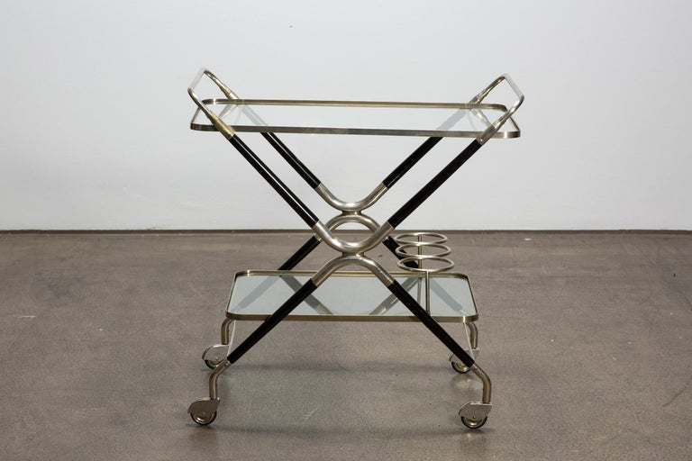 A very beautiful Italian midcentury Design Bar Cart designed by Cesare Lacca in 1940s. This well-crafted piece is made of silver plated brass and black polished shellack wood. Its structure has 2 dimensions with glass shelves and three bottle