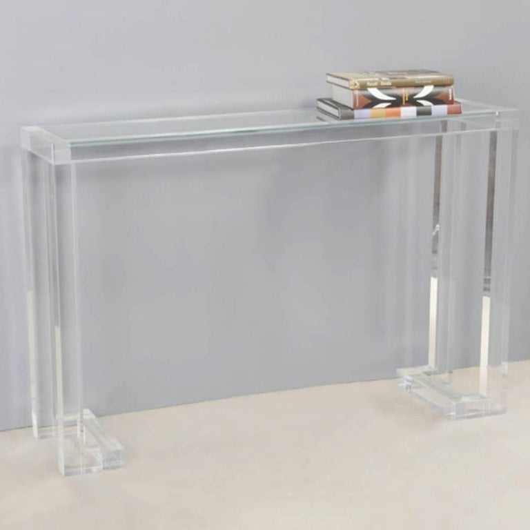 The Ava acrylic and glass console brings sophistication and excitement to a transitional environment. This design looks great as an addition to almost any aesthetic with a pop of modern. Crafted of thick Lucite with an inset glass top. Created by