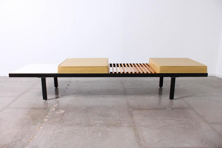 Long steel multi surface bench with two cushions, one wood slated table area and one Formica style table area.