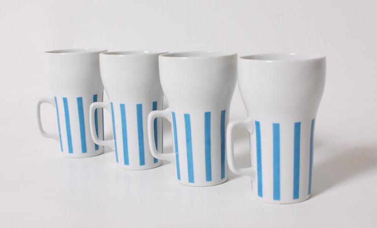 Set of four white mugs and tumbler with blue vertical stripes by Lagardo Tackett. Tumbler measures 10