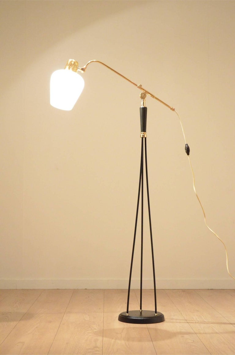 Decorative Mid-Century Scandinavian design floor lamp dating from the early 1950s. Round black painted metal base topped by three metal wires ending with a rotative central part. Adjustable brass arm ending with an opalescent glass pear shaped