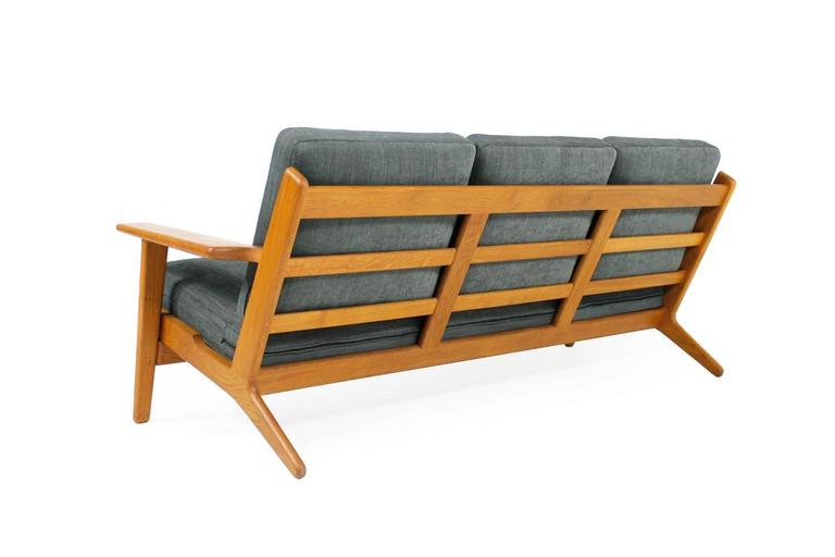 Beautiful Hans Wegner sofa, solid oak, very good condition, newly reupholstered and covered with high quality, soft woven fabric. Innerspring cushions, overall high quality, like all Wegner designed furniture. Model GE 290 and mady by Getama,
