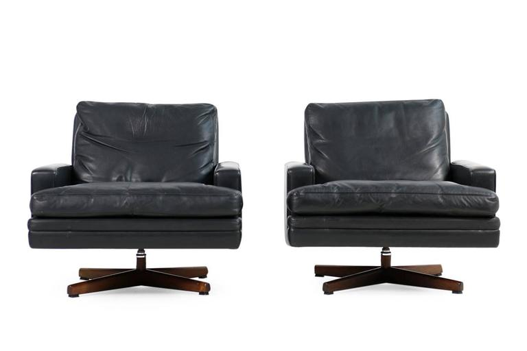 Beautiful and very rare pair of 1960s leather and rosewood swivel lounge chairs, by Fredrik Kayser for Vatne Mobler, Norway. Down filling cushions, metal and wooden base. Fantastic condition, a matching three-seat sofa is available, please visit our