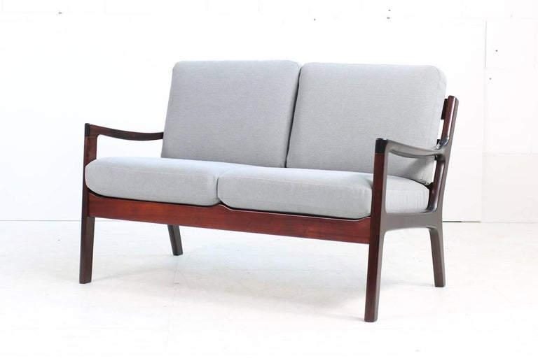 Beautiful 1960s, Ole Wanscher sofa, P.J. Denmark made of mahogany, new upholstery and covered with new high quality cotton fabric in light grey, matching easy chair and three-seat sofa available, please visit our 1stdibs storefront. Some sun fading