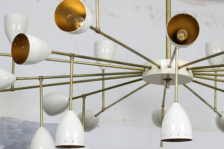Monumental Italian chandelier made of metal and brass with great patina, ecru colored lampshades outside and glittering gold inside, 6ft. of diameter and 4,3ft. high, overall 32 lights for small Edison bulbs. This stunning supernova chandelier looks