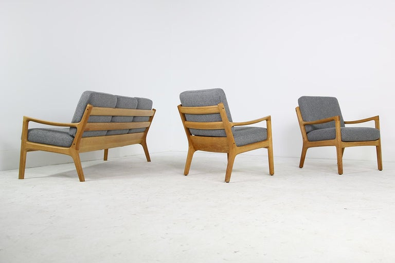 Beautiful set of 1960s Ole Wanscher easy chairs and sofa, senator series - super rare in solid oak. New upholstery in grey woven fabric. Overall a fantastic condition. Made by France & Son, Denmark.