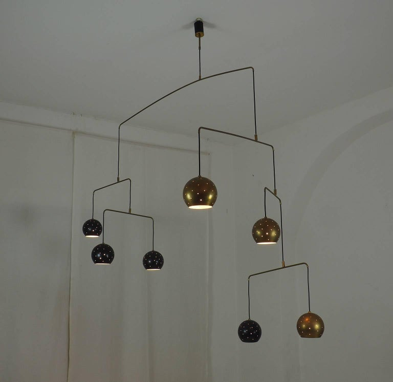 Original Italian brass mobile chandelier manufactured in a very small handcraft production in Milano. 20th Century Large, magic and poetical mobile chandelier with brass and black suspending spheres; it can moves with the flow of air. Wholly in