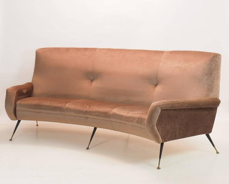 Modern and stylish, Italian, three-seats curved sofa from Milano, 1950s. Designer; Gigi Radice, manufactured by Minotti Milano. Original light brown velvet upholstery in good condition. Black lacquered metal legs with nice brass feet. We can
