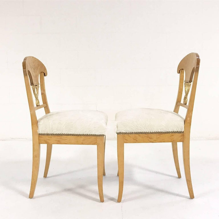 This is a lovely pair of Biedermeier chairs, circa 1820 Austria. We love the blond satin birch and the gilt details. We restored each chair with new foam and upholstered in our natural, silky soft ivory Brazilian cowhide.  Measure: 18