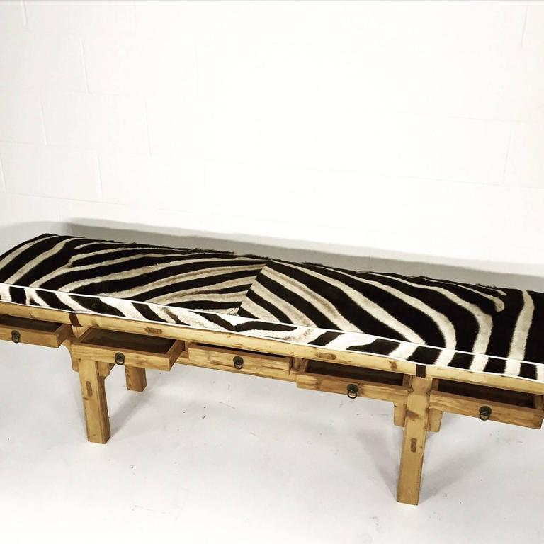 This very cool bench, over 70 years old from the Zhegiang Province, was originally a tall table used to store a calligrapher's tools. We shortened the legs and designed the custom zebra cushion to compliment the beautiful wood.     Length: 68