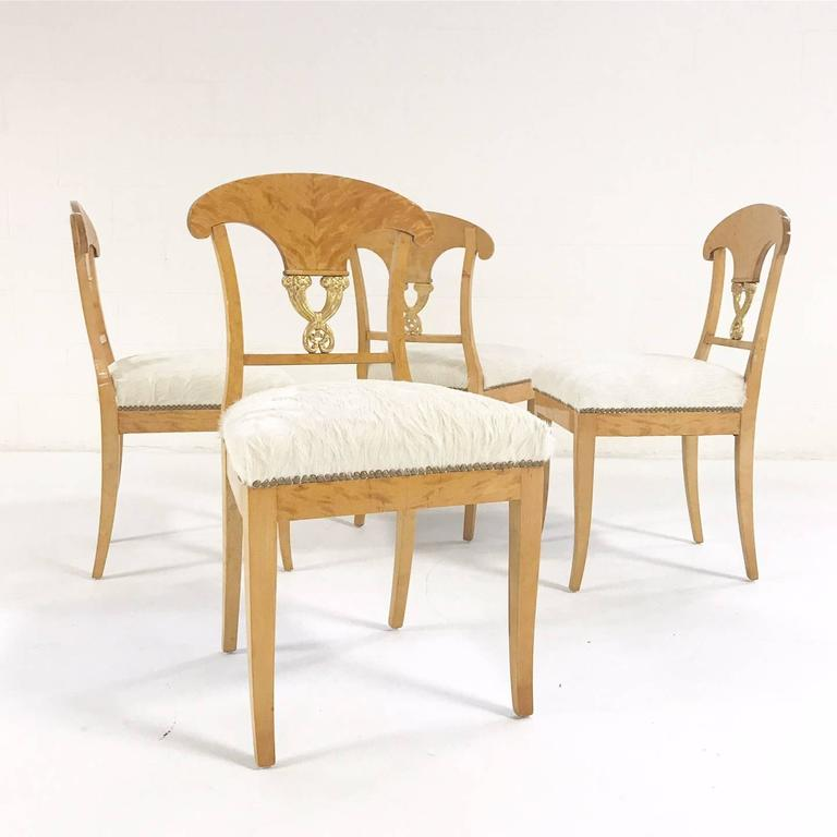 This is a lovely set of four Biedermeier chairs, circa 1820 Austria. We love the blond satin birch and the gilt details. We restored each chair with new foam and upholstered in our natural, silky soft ivory Brazilian cowhide.  Measure: 18