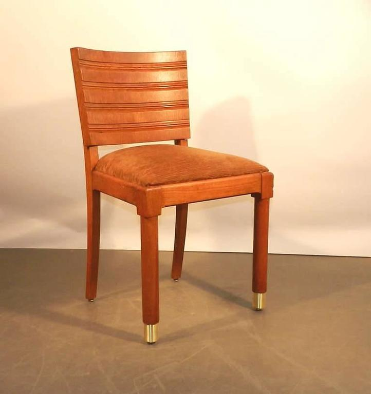 Gaston Poisson, set of ten Art Deco chairs in oak and brass.