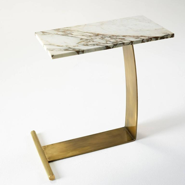 This table is a signature creation of Florentine furniture maker Marioni. The L-shaped brass base supports a lavish white veined marble top.
