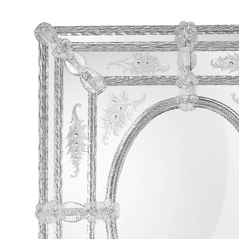 This majestic mirror highlights with timeless sophistication any decor. The rectangular mirror is attached to a wood framework with a natural finish. Its simple structure is masterfully decorated with the use of hand-engraved motifs and Murano glass