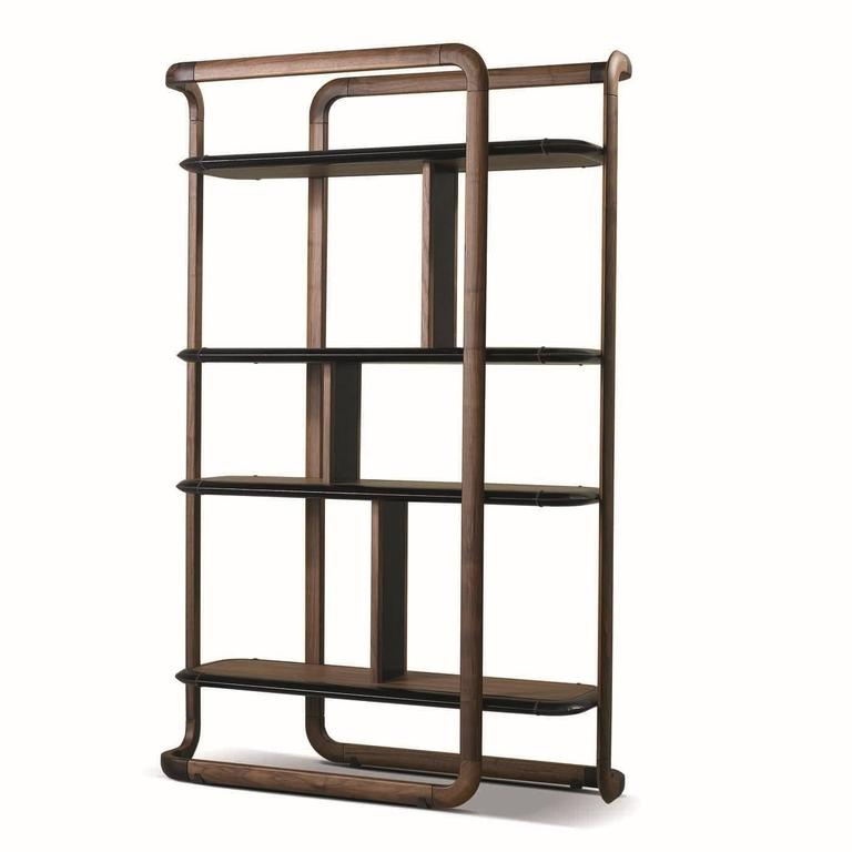 This striking bookcase bears a distinctly modern allure, thanks to its geometric surfaces, made delicate by the round corners at top and bottom. The structure is made entirely in solid walnut wood with four walnut wood shelves placed at different