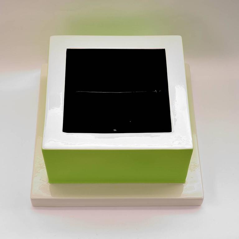 This unique ceramic fruit tray has a glazed base in a glossy white. The tray is glazed in a vibrant green with a matte finish, and glossy white rim. The interior is glazed in a lustrous black. This piece is one in a limited series of 50 crafted in