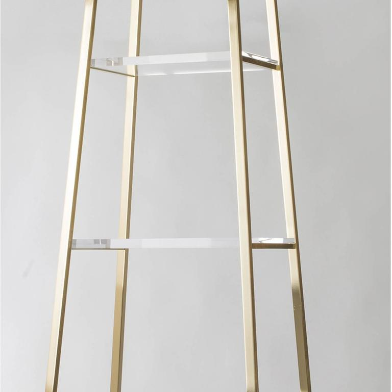This elegant polished brass etagere features five transparent plexiglass shelves of different sizes for a very geometric and Minimalist look. This piece is ideal for every type of interior, both by the walls and off-centered for a more prominent