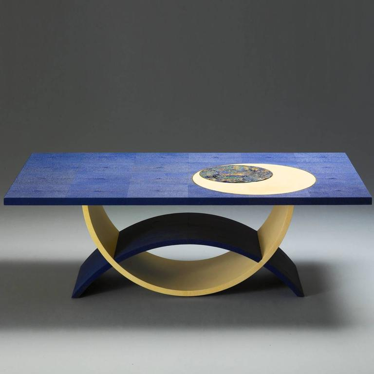 This striking living room table features a top upholstered in blue shagreen (with its distinctive rough texture). The top is embellished with a round insert in azurite stone within a larger round in parchment whose outer profile is highlighted with
