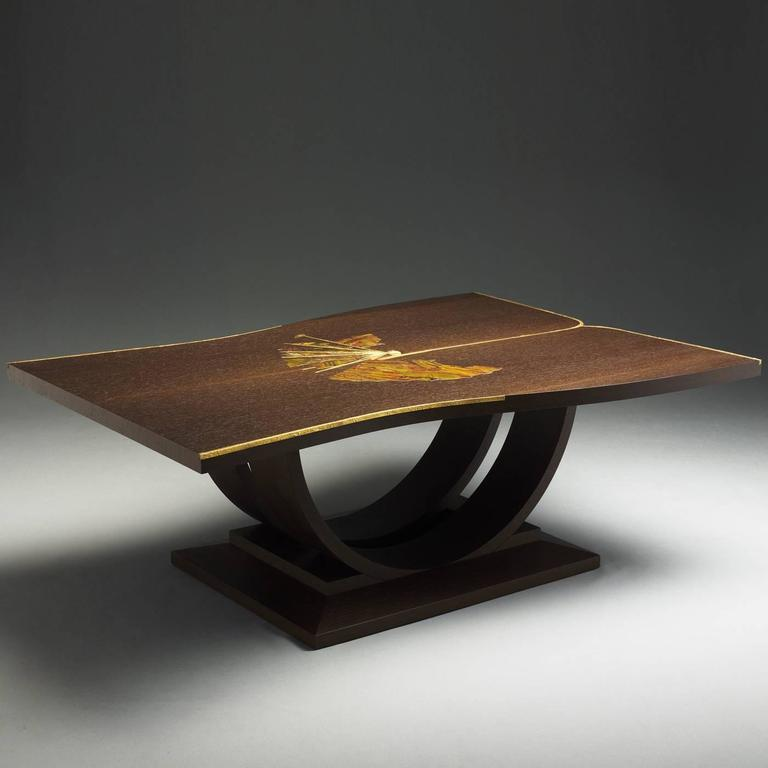 This elegant table is inspired by an ancient kimono and made in wenge wood with the top decorated with a fan in stone. The sticks highlighting the fan and edges of the table are in brass with an orange peel finish. Design Teresa Luni.