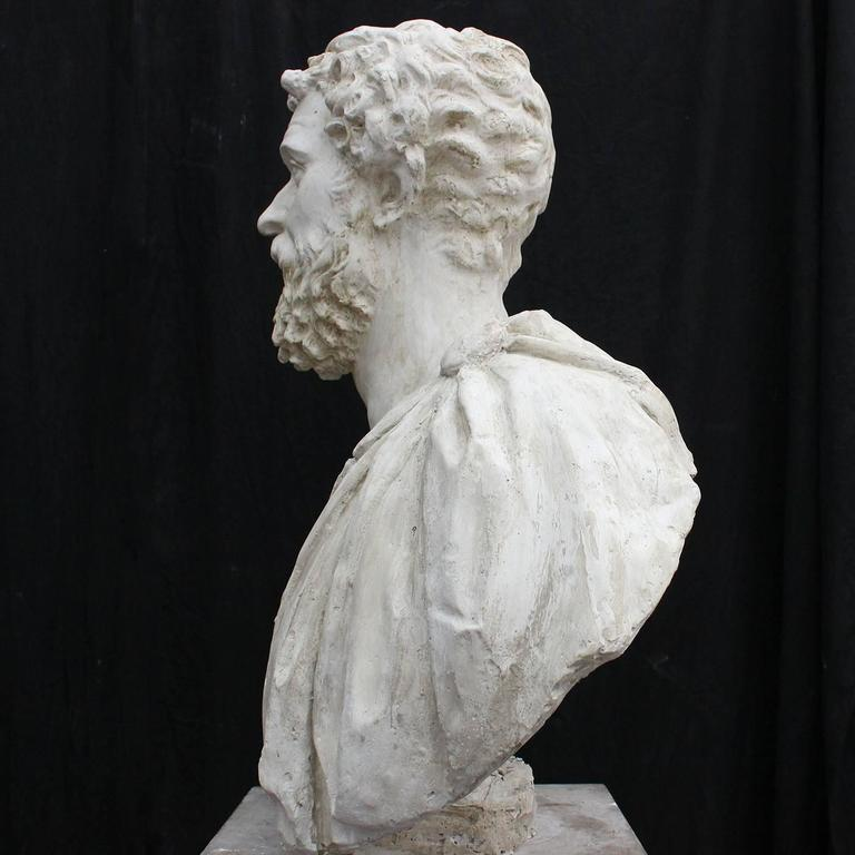 This plaster sculpture is a reproduction inspired by different Roman originals depicting the renowned Roman Emperor Marco Aurelio. The Emperor is dressed in his military uniform featuring a Medusa and is shown looking upwards, a pose symbolizing his