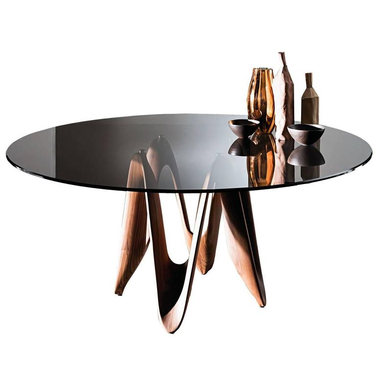 This elegant table features a geometric base made of four connected walnut wood elements that support in the centre a round top in tinted glass.
