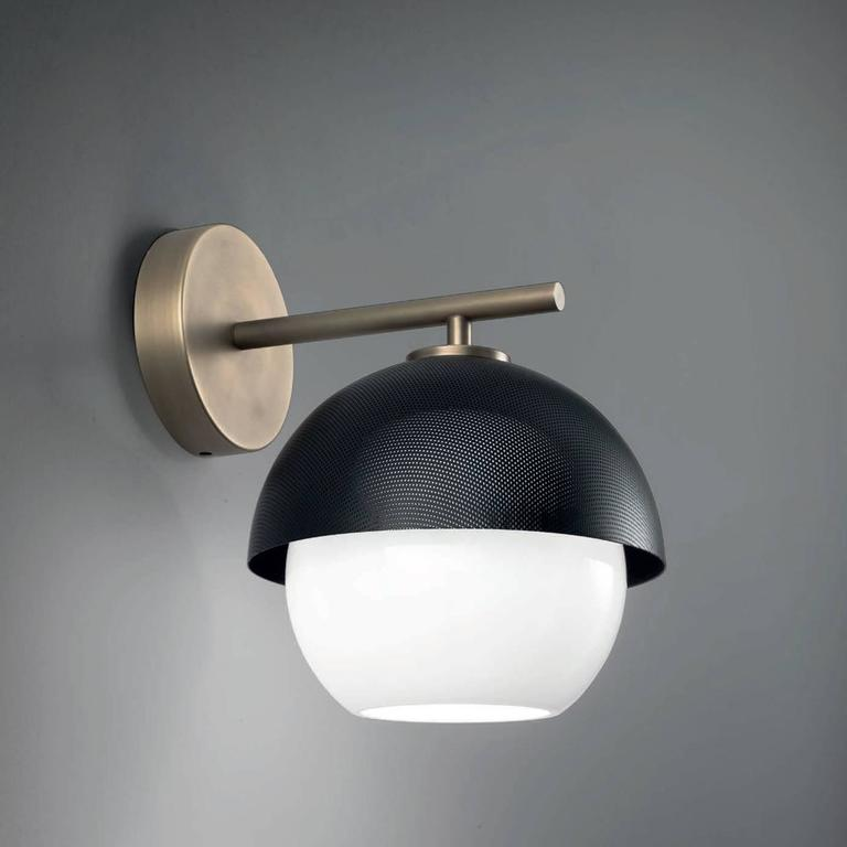 This sophisticated sconce has a brass structure in a light or dark burnished finish that supports a semi-spherical shade facing downwards and made in metal that can be either given a matte black or a matte golden finish, for a warmer final effect.