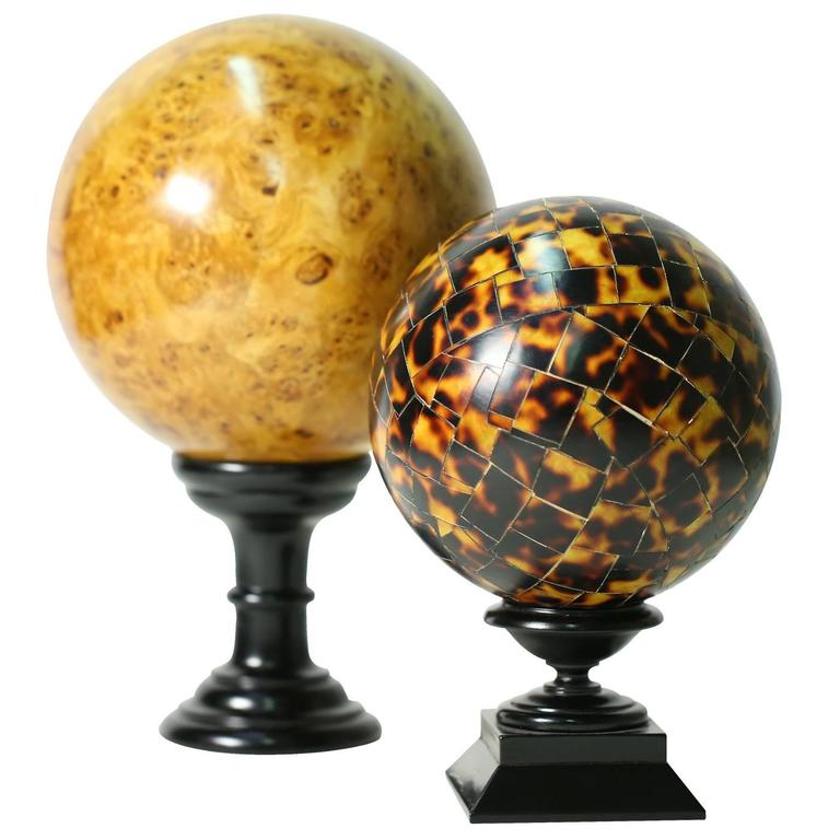 Exquisite sphere with a wood inlay imitating a tortoiseshell, finished in a glistening wax patina with varying shades of red, orange and black, that play with light. The sphere fitted with a black support in the shape of a chalice.