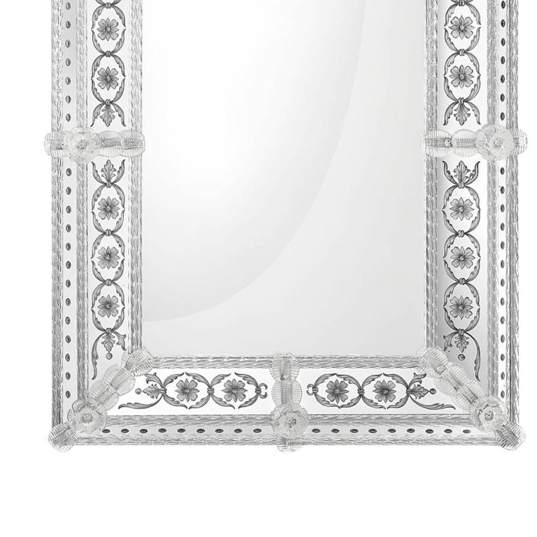 This elegant object of art was designed by Leo De Carlo and expertly executed by master glass makers on a solid wood structure with a natural finish. Its simple rectangular mirror with an antique finish is enclosed in an exquisite frame adorned in
