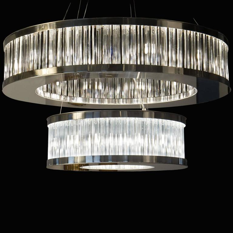 This striking two tier chandelier features a lustrous chromed metal finish. It's larger upper tier mixes black linear elements in with the transparent glass, creating interesting effects when lit. The smaller lower tier uses solely transparent