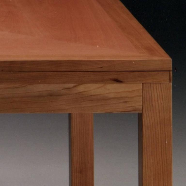 This elegant extendible table has a square top that features cherrywood with delicate inlays in pear wood. It can also be made in walnut wood with inlays in maple wood. If the preference is for the consistent look given by one type of wood only, it