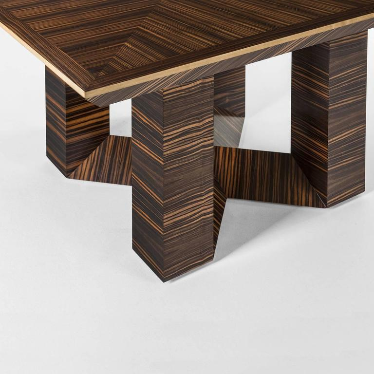 This table is in a unique octagon-shaped top which sits on top of a solid ebony macassar wood structure. The top features a pattern in the same wood, with the wood grain crossing, creating striking geometric shapes. The boarder of the table is in