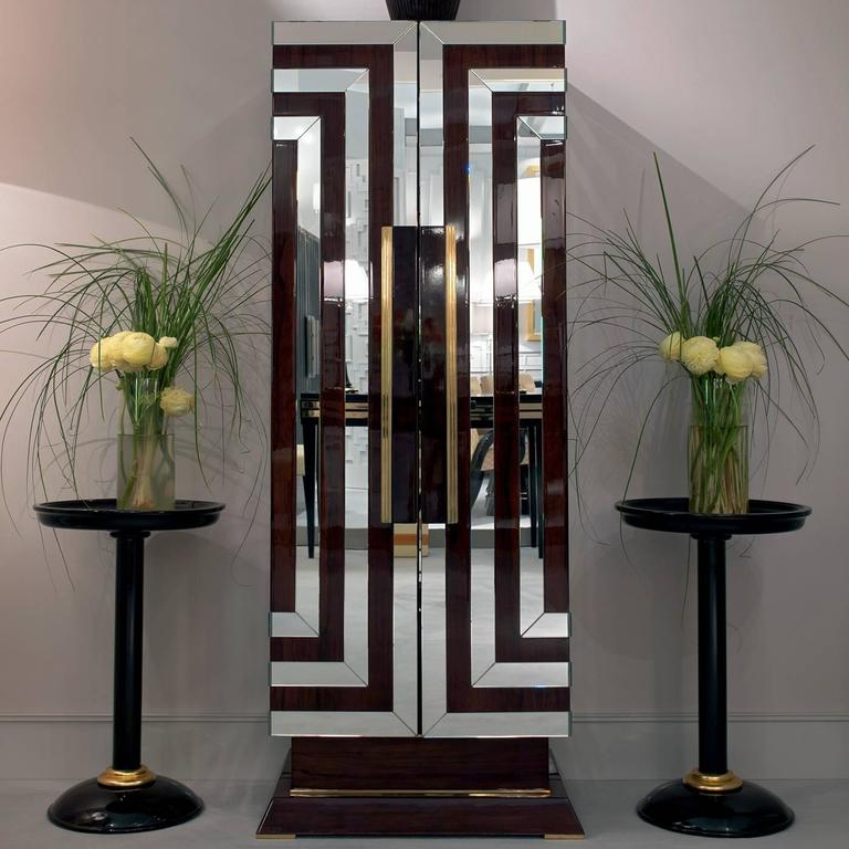 This exquisite bar cabinet is inspired by the bold and sophisticated style of Art Deco, with its geometric volumes and decorations, and its polished reflective surfaces. The glossy walnut wood structure is adorned with a series of concentric lines