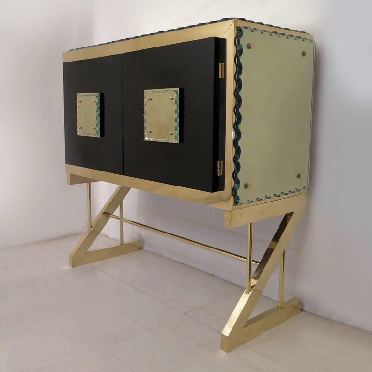 This console will perfectly complement a contemporary home. This piece combines both classic and modern shapes and colors, in order to produce a unique look. The underlying wooden structure of the rectangular top is covered in brass plates, along