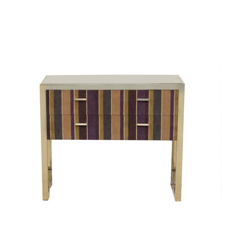 Inspired by the Art Deco style, the external structure of this elegant chest of drawers is in brass with a brushed finish. The interior is entirely made in wood upholstered with a luxurious silk velvet cover. The exterior is covered on the side and