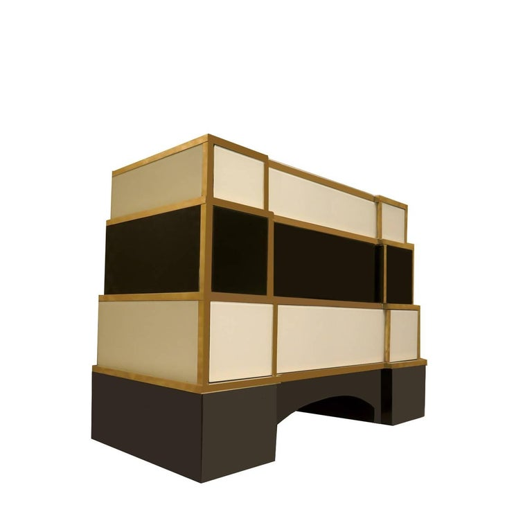 The unique design of this chest of drawers is enhanced by the glass and brass cover of its wooden structure. The black and white color combination of the glass panels that entirely cover this piece is chic and timeless and their smooth surfaces are