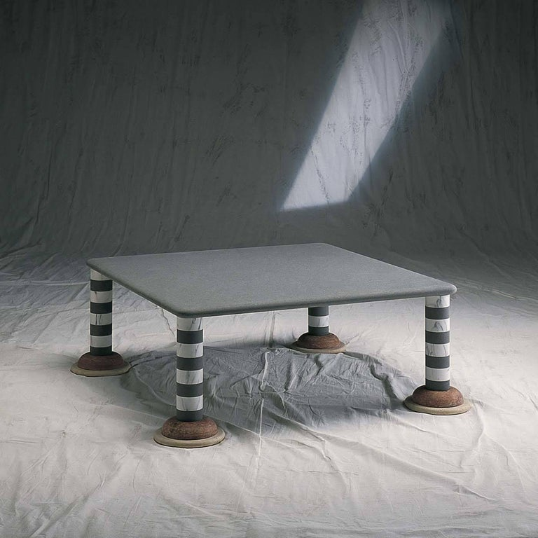 A striking, original design by Michele De Lucchi featuring a square top in pietra serena (gray sandstone) with rounded edges supported by four cylindrical legs in a striped pattern of white Carrara marble and gray sandstone. The visually striking
