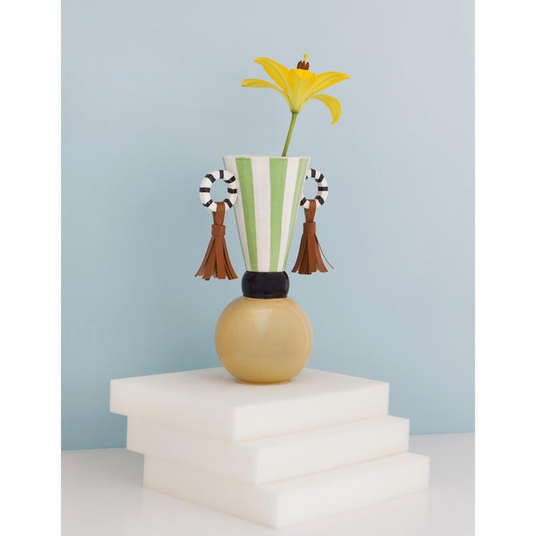 This striking vase is part of the Masai collection, inspired by the decorative elements of this African tribe that are interpreted in a modern way and exquisitely made into objects of functional decor. The ceramic body of this piece is handmade and