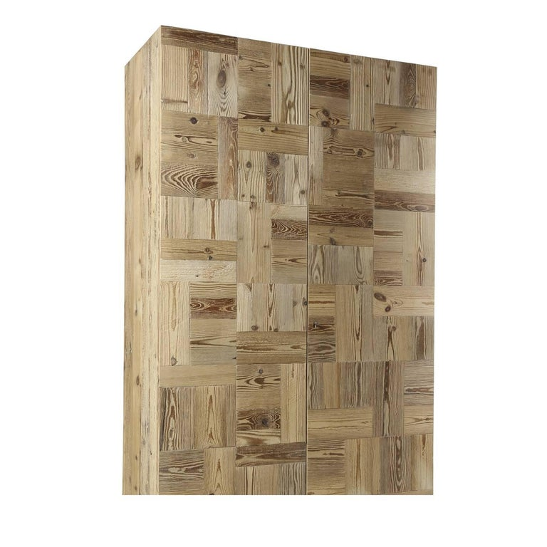 This striking two-door wardrobe, made entirely of antique recycled fir wood, combines panels of three different shades of wood in a layered pattern creating an impressive mosaic decoration. The interior is complete with a hanger rob and three