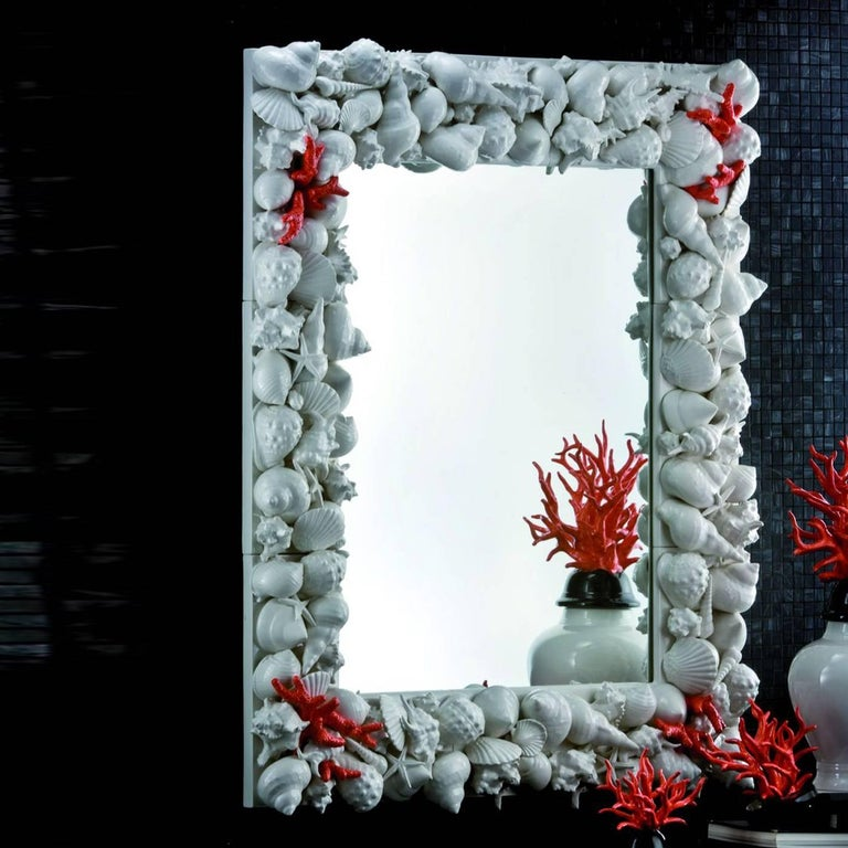 The magnificent frame around this rectangular mirror is decorated with the application of shells of different sizes and shapes, all with a polished white finish. A few accents of coral-shaped decorations add striking red accents to the piece.