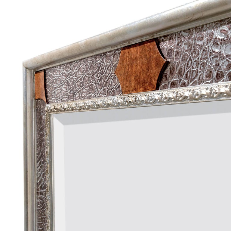 This mirror features a wooden structure with a rectangular silhouette adorned with silver leaf that was given a striking crocodile texture. The piece boasts inserts in crocodile leather (caiman crocodilus kakare) and briar root and moldings oat the