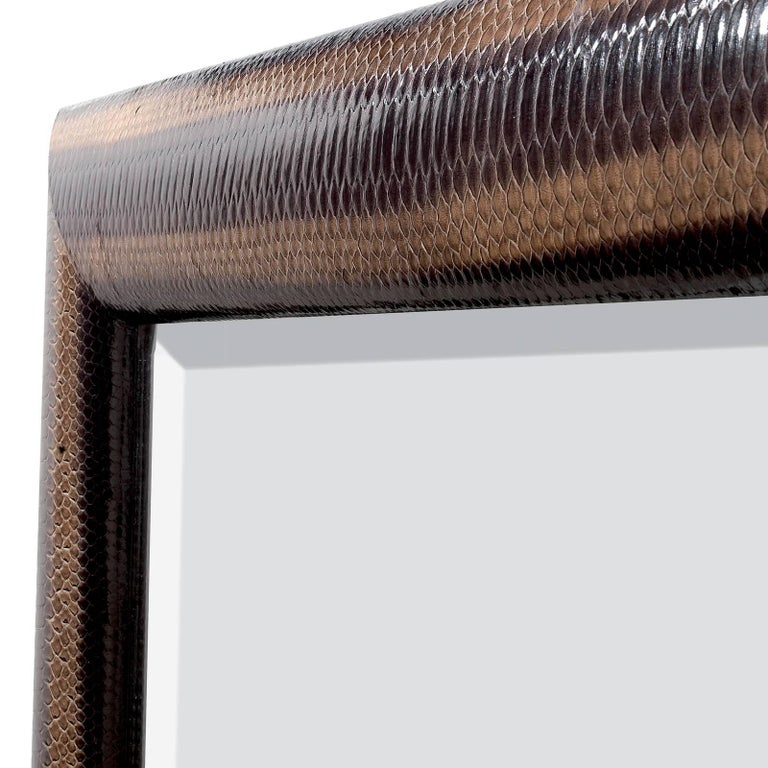 The frame is upholstered in genuine python leather, while the structure and the back are in wood. The mirror, with Minimalist moldings at the edges, is enclosed in a stunning frame covered in a dark shade of python.