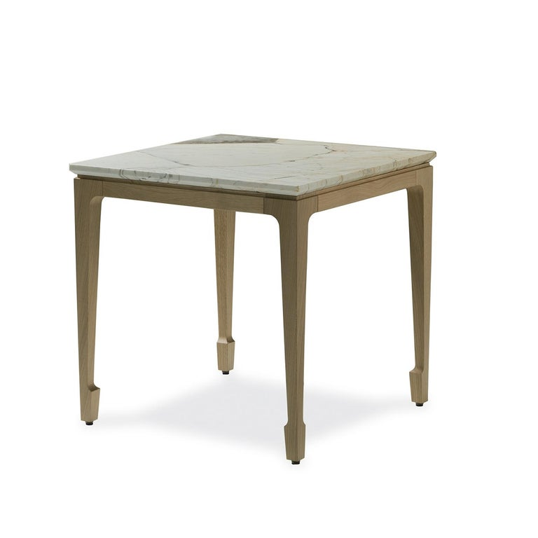 This eye-catching side table is part of the Yang collection. It is crafted of durmast with a natural finish and its geometric silhouette comprises four legs with a sculptural decoration at the base with a marble top that rests on it. The smooth
